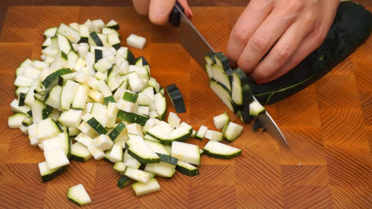 Сначала подготовим все ингредиенты: Цукини разрезаем сначала вдоль, а затем нарезаем кубиками размером примерно 1 см. Так как у меня молоденькие цукини, то шкурку я не срезаю и  не вынимаю семена. Если салат готовить из более старых цукини с уже жесткой шкурой и затвердевшими семенами, то ее нужно срезать и семена удалить. Также вместо цукини можно смело использовать кабачки. Для салата понадобится 3 кг нарезанных цуккини или кабачков.