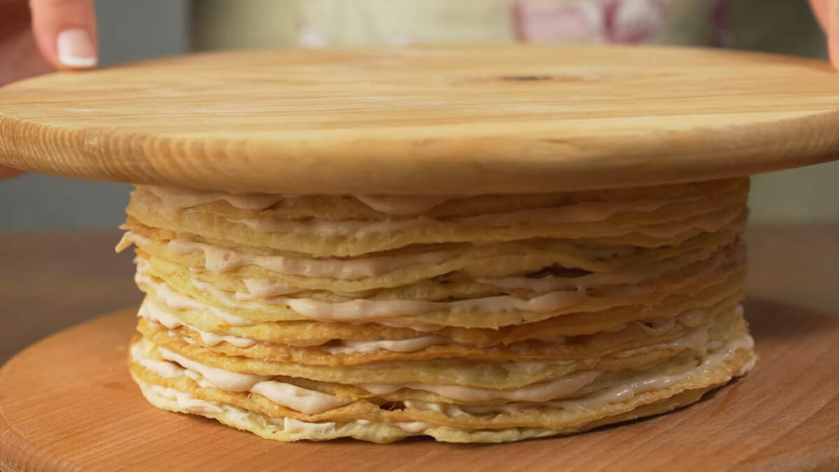 Сверху торт накрываем доской, чтобы он получился ровный сверху. Ставим торт в холодильник настаиваться примерно на 4 часа, можно дольше.