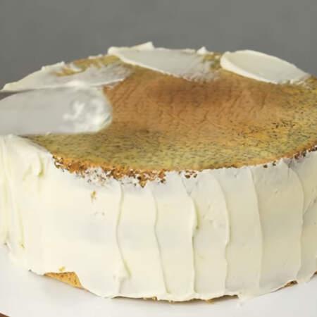 Торт покрываем тонким слоем крема, чтобы прибить все крошки. Сначала наносим крем, а затем выравниваем широким шпателем.