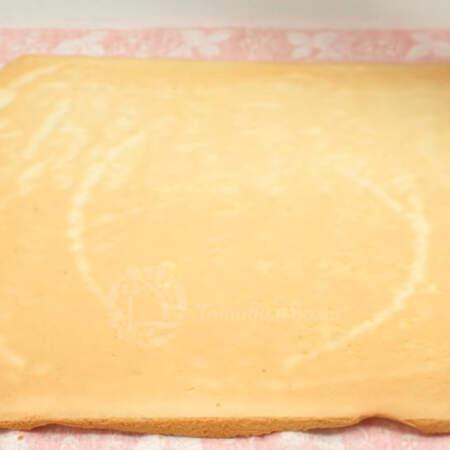 Бисквит уже испекся, сразу же, пока он еще горячий, кладем его на чистое полотенце и снимаем с него пергаментную бумагу.
