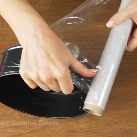 Сначала подготовим емкость для приготовления торта. Разъемную форму для торта обматываем пищевой пленкой сначала по бокам и подворачиваем вниз, для того, чтобы жидкость не протекла через форму.