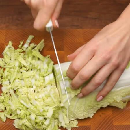 Берем полкочана пекинской капусты, разрезаем его пополам и шинкуем небольшими кусочками.