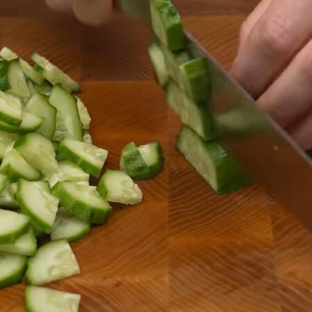 Сначала подготовим все ингредиенты для салата. 2 огурца среднего размера разрезаем пополам и нарезаем четверть кружочками.