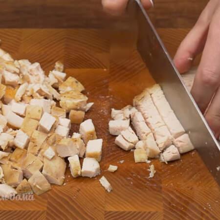 Одну запеченную куриную грудку, весом 400 г, разрезаем сначала на пластинки, а затем пластинки нарезаем небольшими кубиками.