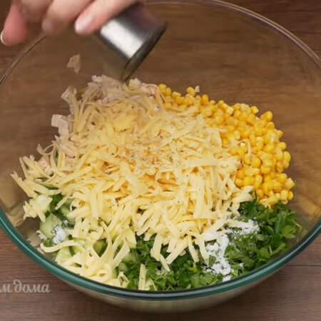 В миску насыпаем нарезанные огурцы, подготовленное мясо, 1 банку консервированной кукурузы, измельченную петрушку и тертый сыр. Салат немного солим и перчим черным молотым перцем. Заправляем салат 2 ст.л. сметаны.