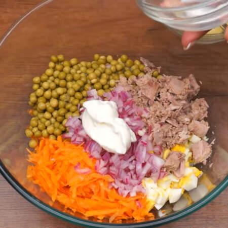 В миску насыпаем тертую морковь, нарезанные яйца, 1 банку консервированного зеленого горошка, кладем кусочки тунца и насыпаем маринованный лук. Салат немного солим. Заправляем 1 ст.л. несладкого салатного йогурта и 1 ст.л. майонеза.