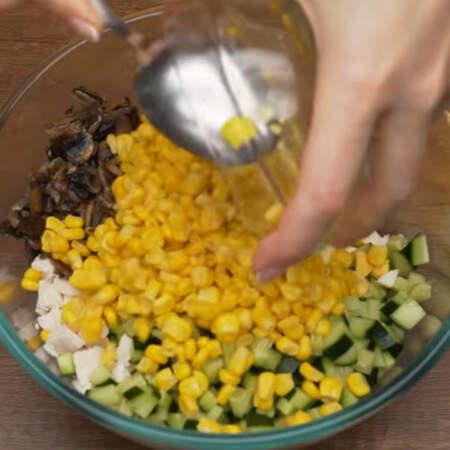 В большую миску кладем подготовленное куриное филе, нарезанный огурец, уже остывшие жареные шампиньоны, нарезанные яйца и 1 банку консервированной кукурузы. Салат заправляем примерно 2 ст. л. майонеза