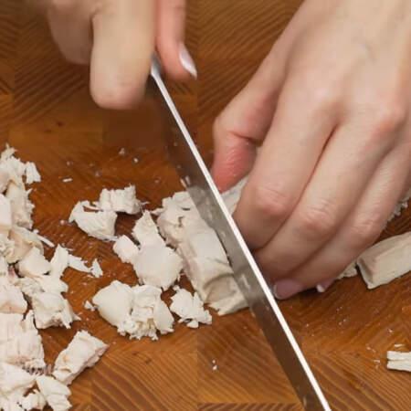 Одно вареное куриное филе, весом примерно 300 г, тоже нарезаем пластинками,  а затем небольшими кубиками.