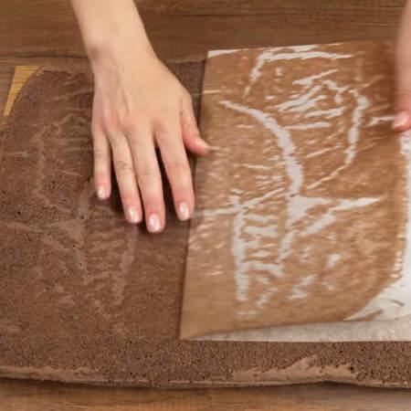 Испекшийся бисквит вынимаем из духовки и сразу же перекладываем на доску, снимаем пергаментную бумагу.