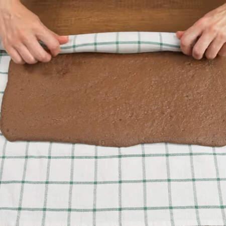 Бисквит перекладываем на чистое и сухое кухонное полотенце. Скручиваем еще горячий бисквитный корж в рулет вместе с полотенцем. Все оставляем в таком виде пока не остынет бисквит.