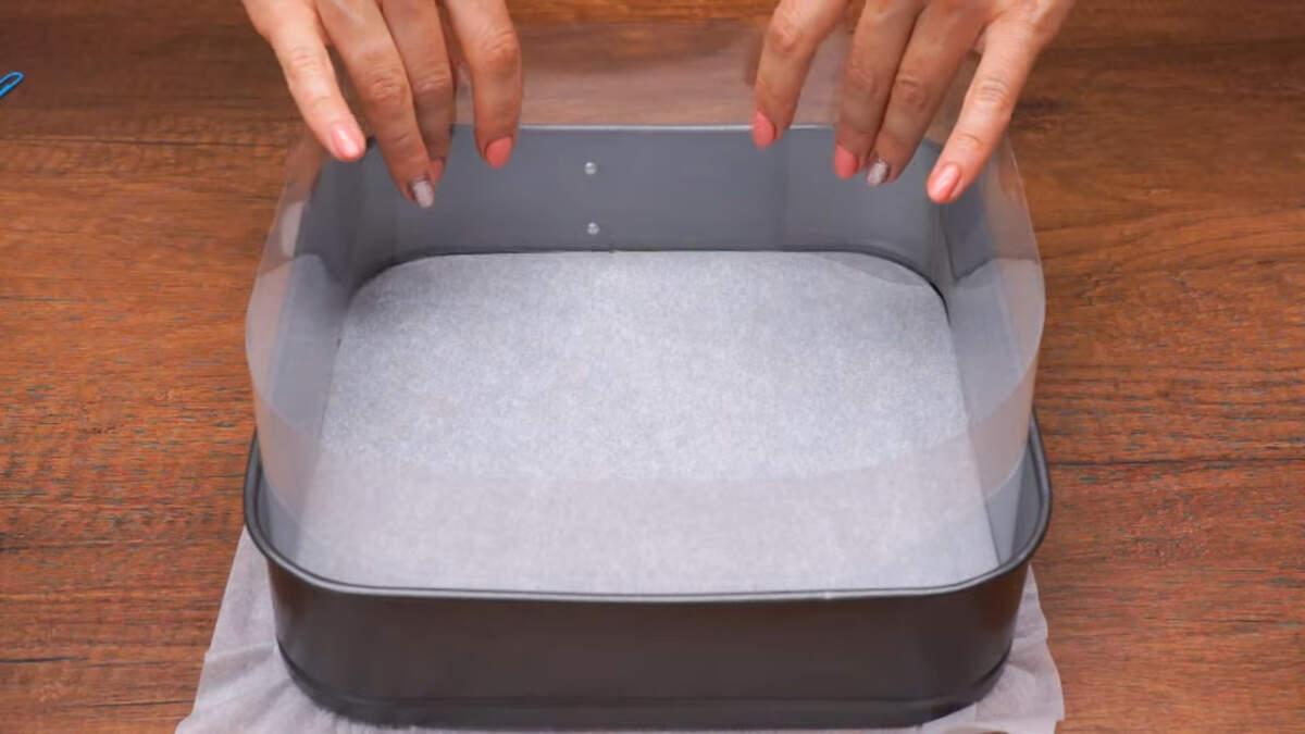 Сначала подготовим форму в которой будем собирать торт. Дно формы застилаем пергаментной бумагой. У меня квадратная форма размером 24 *24 см.  По бокам формы ставим ацетатную пленку. Если нет ацетатной пленки, то можно вместо нее поставить пергаментную бумагу.