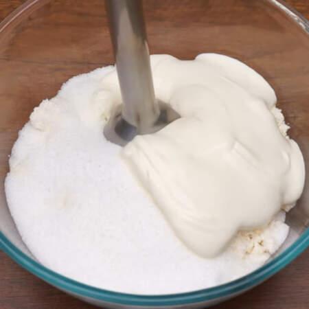 В миску насыпаем 500 г творога, сюда же добавляем 10 г ванильного сахара, 300 г сахара и наливаем 100 мл сметаны или густого йогурта.