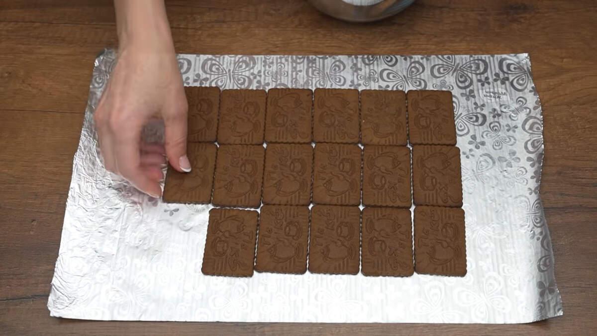 Складываем торт. На стол кладем фольгу. На фольгу выкладываем шоколадное песочное печенье в три ряда. В каждом ряду по 6 печений. Всего для торта понадобится 36 печений.
