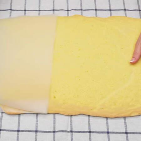 Бисквит вынимаем из духовки и сразу же перекладываем на полотенце. Снимаем с бисквита пергаментную бумагу.