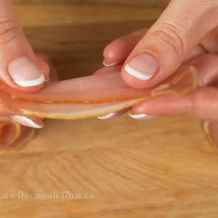 Вторыми приготовим бутерброды с балыком. Берем ломтик балыка, складываем его вдоль и сворачиваем.