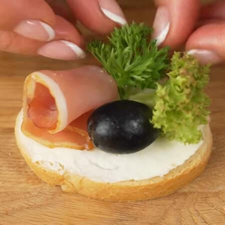 Берем багет и смазываем его сливочным сыром. На подготовленный ломтик хлеба выкладываем с одной стороны цветок из балыка, с другой стороны листья салата. По центру кладем черную оливку без косточки и листики петрушки.