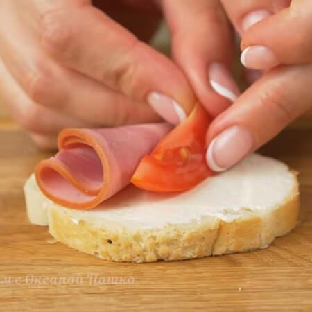 Складываем бутерброд. Берем уже подготовленный ломтик батона. Сбоку выкладываем цветок из колбасы. Посредине кладем дольку помидора. От салатного листа отрезаем верхнюю часть. Скручиваем ее и кладем на бутерброд. Таким методом складываем все бутерброды.