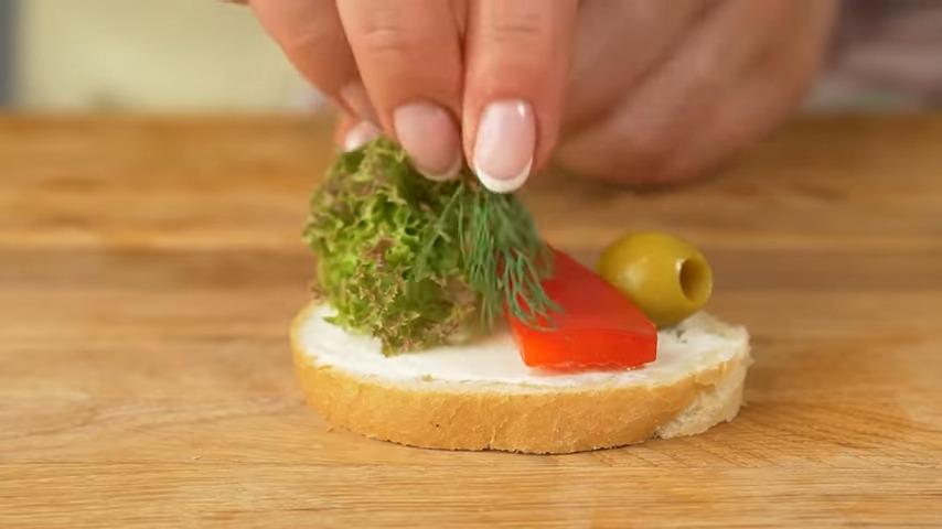 На бутерброд с одной стороны выкладываем листья салата. По центру кладем треугольник перца. С другой стороны бутерброда ставим зеленую оливку. И украшаем укропом. Так готовим все бутерброды.