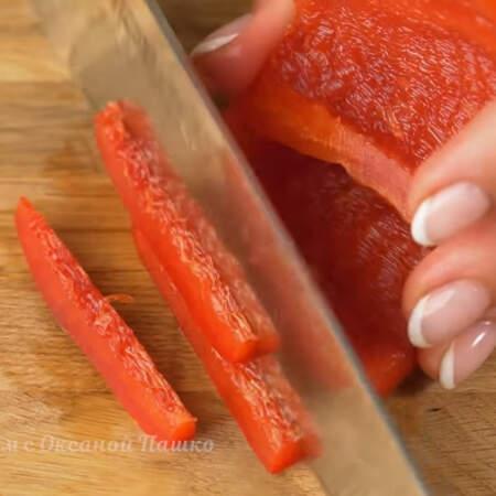 Берем перец и отрезаем у него верхнюю и нижнюю части. Вырезаем семенную коробочку. Перец нарезаем на тонкие полоски.