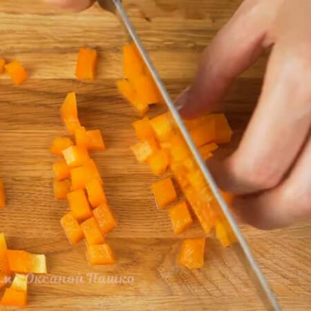 Перец нарезаем сначала полосками, а затем полоски режем небольшими кубиками. Я взяла один красный и один оранжевый перец.