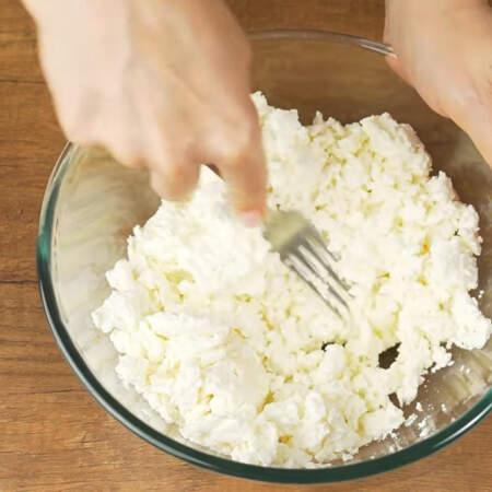 В большую миску насыпаем 800 г творога. Творог можно использовать любой жирности. Вилкой разминаем творог, чтобы измельчить крупные склеившиеся кусочки. По желанию творог можно измельчить погружным блендером. Творог желательно достать из холодильника за 10-15 минут до приготовления, чтоб он немного согрелся. Тогда при введении желатина не будут образовываться желатиновые комочки.