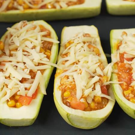 Сверху каждый кабачок с начинкой посыпаем тертым сыром.