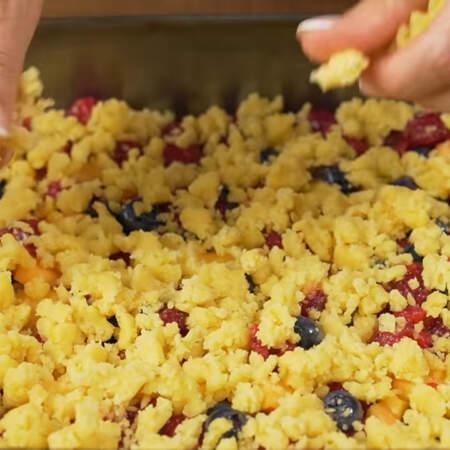 Вынимаем из холодильника часть теста которую оставляли. Отрываем от него небольшие кусочки и кладем на ягоды. По желанию это тесто можно заморозить и натереть на терке.