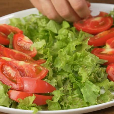 На дно овального блюда кладем нарезанные листья салата. Распределяем его по всему блюду. На салатные листья, немного отступив с каждого края, кладем дольки помидоров формируя из них полоски.