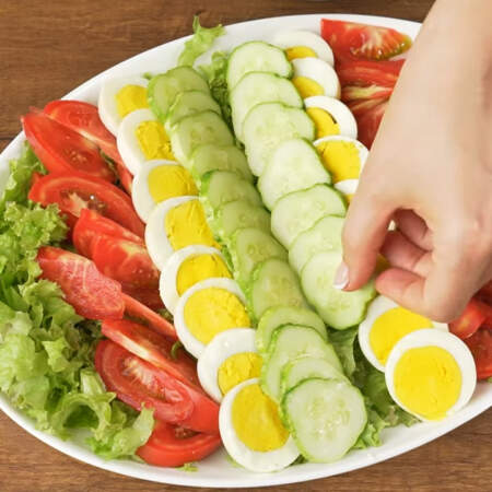 Возле помидоров, ближе к центру выкладываем кружочки яиц. В самом центре блюда выкладываем 2 ряда кружочков огурцов.