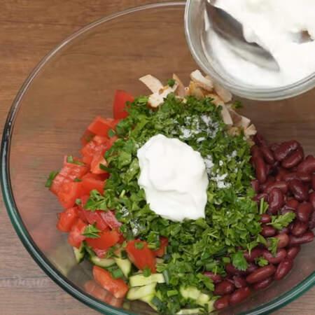 В миску высыпаем нарезанные огурцы, помидоры, куриное филе и 1 банку консервированной фасоли. Сюда добавляем подготовленный зеленый лук и петрушку. Салат солим по вкусу. Заправляем 2-3 ст. л. не сладкого густого йогурта.