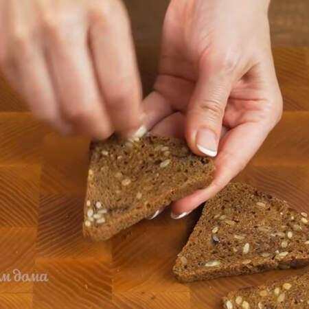 Берем три ломтика черного хлеба, я уже подсушила его в тостере и натираем его чесноком со всех сторон. Также хлеб можно немного подсушить на сковороде.