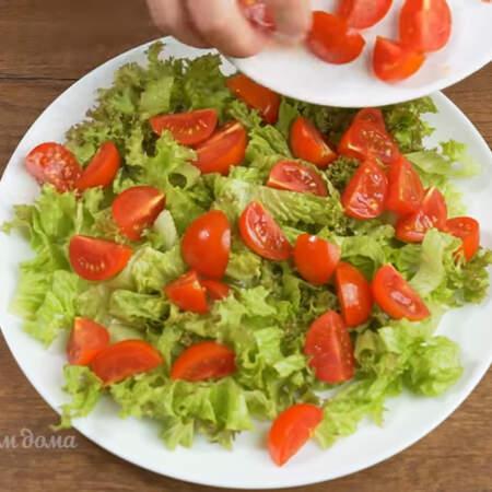 На дно большой плоской тарелки кладем нарезанные листья салата. Диаметр моей тарелки 25 см. На салат выкладываем нарезанные помидоры.