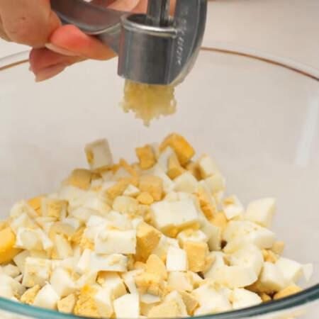 В миску кладем нарезанные сердечки, вареные яйца и выдавливаем 2 зубчика чеснока через пресс.