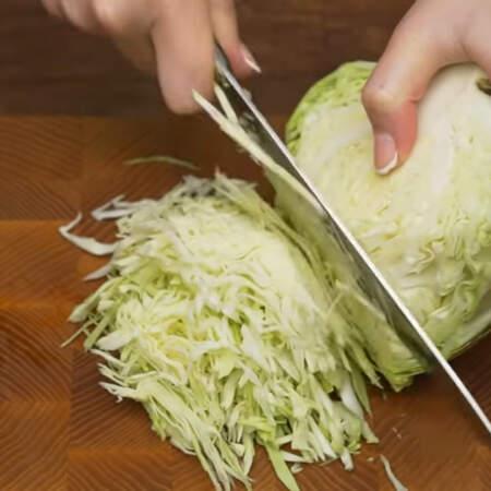 Примерно пол кочана молодой белокочанной капусты мелко шинкуем ножом.