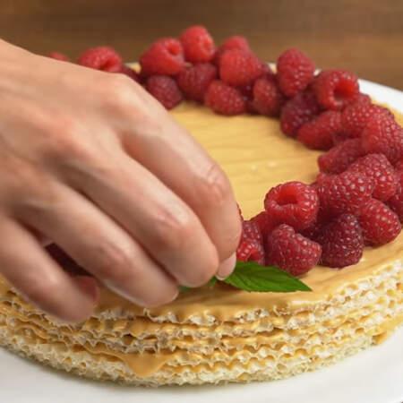 По кругу торта выкладываем ягоды малины. Также торт украшаем листиками мяты. Торт готов, можно подавать на стол.