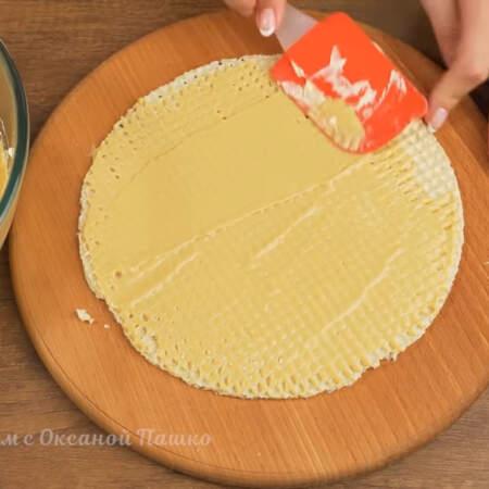 Складываем торт. Кладем вафельный корж и смазываем его кремом. Удобнее всего наносить крем силиконовой лопаткой. Крем толстым слоем наносить не нужно, достаточно просто замазать кремом все углубления в вафельном корже. Остатки крема снимаем  в миску.
