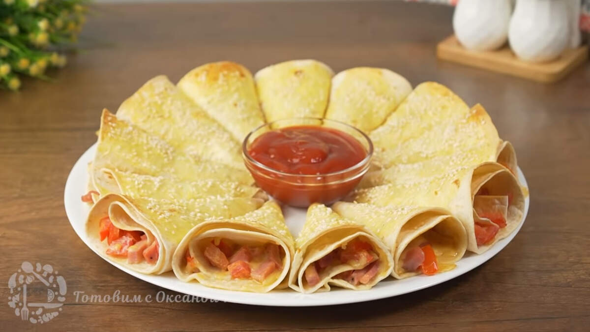 Готовую закуску достаем из духовки и перекладываем на большое блюдо. По середине ставим пиалу с соусом или кетчупом.