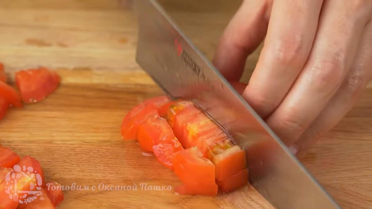 2 помидора среднего размера разрезаем пополам и вырезаем плодоножку. Помидоры тоже нарезаем сначала пластинками, а затем пластинки режем кубиками.