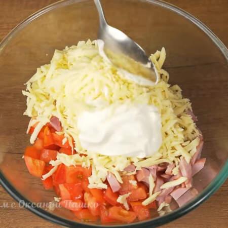 В миску насыпаем подготовленные помидоры, нарезанную ветчину и тертый сыр. Сюда же добавляем примерно 2 ст.л. сметаны.