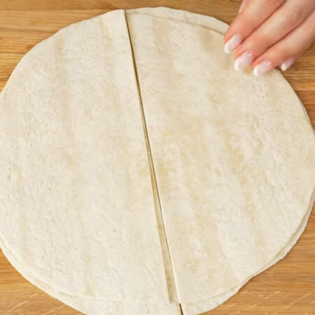 Берем 7 листов тортильи и разрезаем их пополам на 2 одинаковые части.