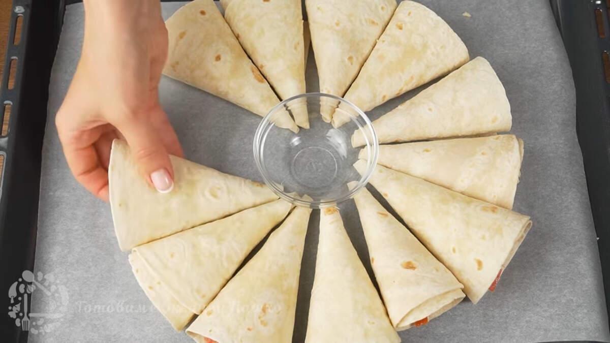 Берем противень от духовки и кладем на него пергаментную бумагу. По центру ставим пиалу для соуса, перед тем, как ставить противень в духовку, пиалу нужно убрать. Вокруг пиалы выкладываем все кулечки с начинкой.