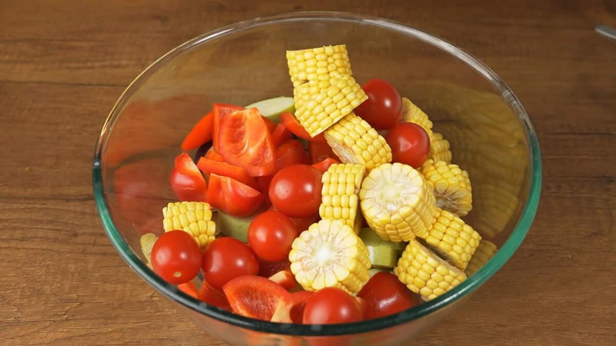 В большую миску кладем баклажаны, кабачки, перец, нарезанные початки кукурузы, и 300 г помидоров черри.
