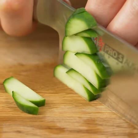 Сначала подготовим все ингредиенты для салата. 2 огурца среднего размера разрезаем сначала вдоль на пластинки, а затем пластинки нарезаем брусочками.