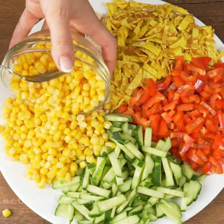 Складываем салат. Берем большое блюдо и небольшим сектором выкладываем на него нарезанное мясо. Диаметр моего блюда 32 см. Затем кладем подготовленные яйца. Следующим выкладываем сладкий перец. Дальше нарезанные огурцы. И последней выкладываем одну баночку консервированной кукурузы.