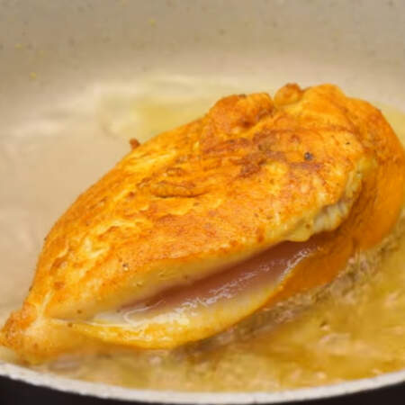 Когда мясо поджарилось с двух сторон, наливаем в сковороду полстакана кипятка и накрываем ее крышкой. Огонь уменьшаем до минимума и тушим филе под крышкой примерно 15-20 минут.