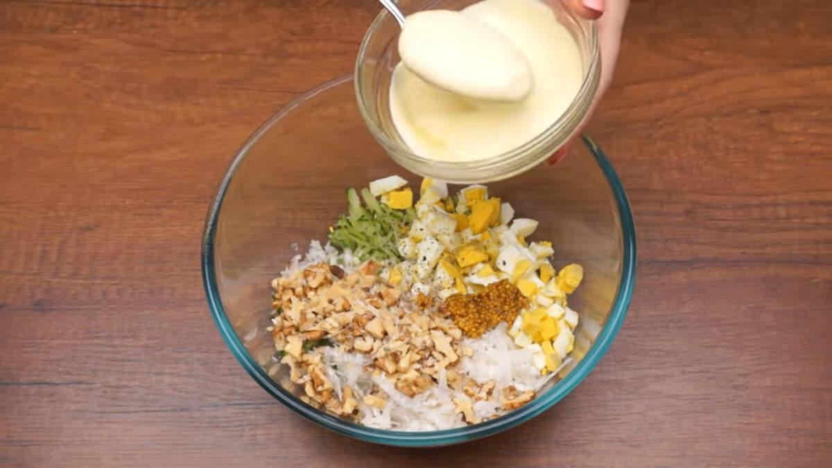 В миску кладем уже подготовленный огурец, тертый дайкон, яйца и насыпаем орехи. Салат немного солим и перчим по вкусу. Также сюда добавляем 1 ч.л. французской горчицы зернами или обычную горчицу. Салат заправляем 1 ст. л. майонеза и хорошо перемешиваем. Вместо майонеза салат можно заправить сметаной или густым несладким йогуртом.