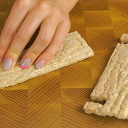 Для того, чтобы салат выглядел красиво, подавать его будем в хлебцах. Для этого в каждом кусочке аккуратно делаем ножом вырезы.