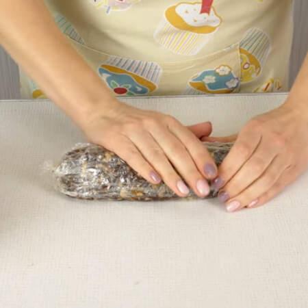 Сладкую массу заматываем в пленку и придаем ей форму колбаски, плотно утрамбовывая.