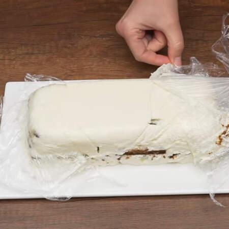 Торт застыл. Снимаем пищевую пленку и переворачиваем его на блюдо. С торта аккуратно снимаем пленку. Б