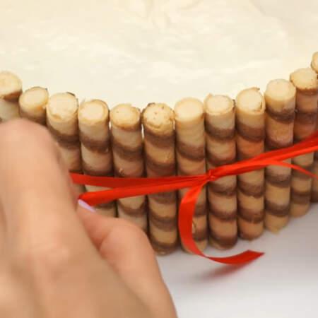 Для того, чтобы трубочки случайно не упали и для красоты, перевязываем торт красной атласной ленточкой.